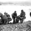 Members of an American landing unit help their exhausted comrades ashore during the Normandy invasion, June 6, 1944. The men reached the zone code-named Utah Beach, near Sainte Mere Eglise, on a life raft after their landing craft was hit and sunk by German coastal defenses. (AP Photo)