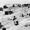 Sitting in the cover of their foxholes, American soldiers of the Allied Expeditionary Force secure a beachhead during initial landing operations at Normandy, France, June 6, 1944. In the background amphibious tanks and other equipment crowd the beach, while landing craft bring more troops and material ashore. (AP Photo/Weston Hayes)