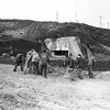 """One year after the D-Day landings in Normandy, German prisoners landscape the area around a former German pill box at Saint-Laurent-sur-Mer, France, near """"Omaha"""" Beach, May 28, 1945. The pill box, with a knocked out gun still visible, will be made into a monument dedicated to U.S. assault forces. (AP Photo/Peter J. Carroll)"""