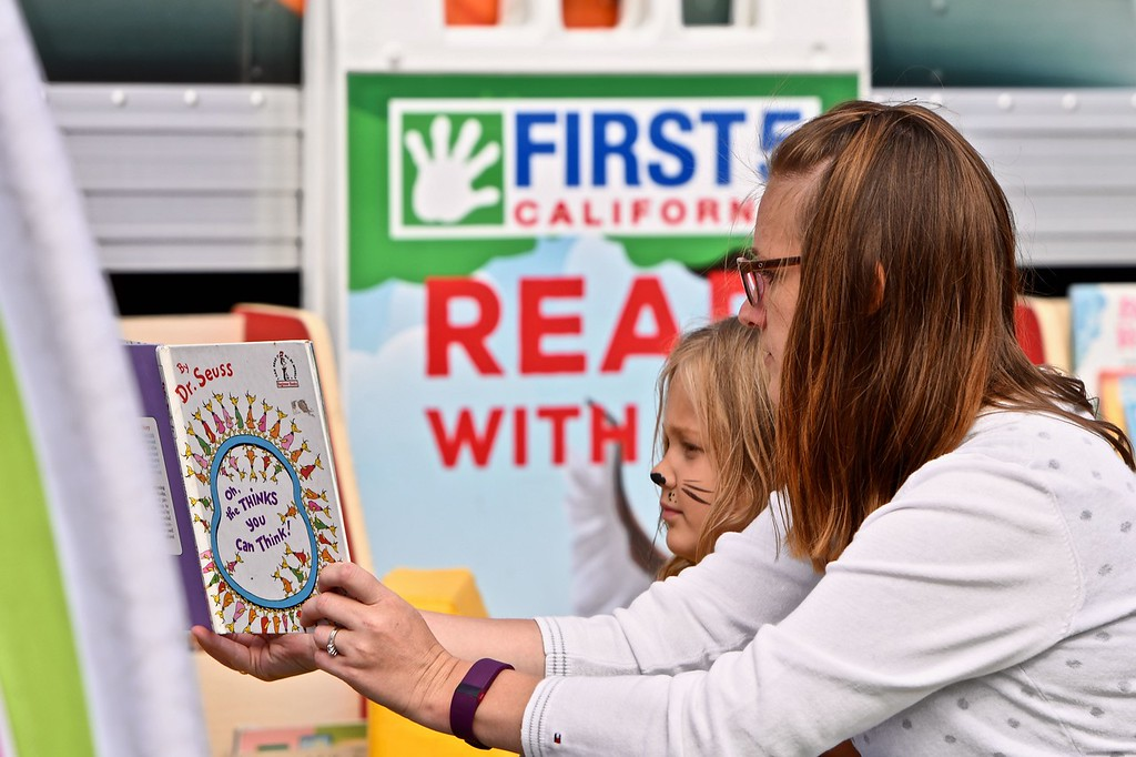 . Nikki Rutland reads to Abigail Rutland, 5, at a First 5 California hosted booth encouraging parents to read more to their children as part of the street carnival for the Apple Harvest Festival. José Quezada�For Times-Standard