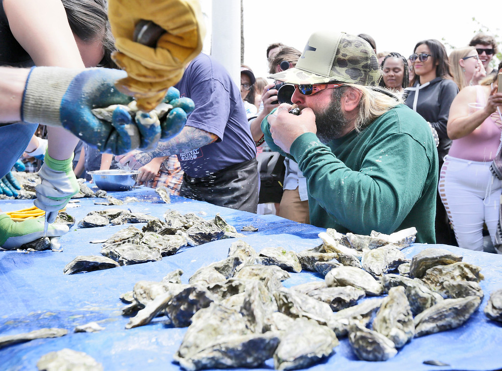 . Shaun Walker � The Times-Standard  Sebastian Elrite, right, eats oysters that Felicia Tom opens in the Shuck and Suck contest.