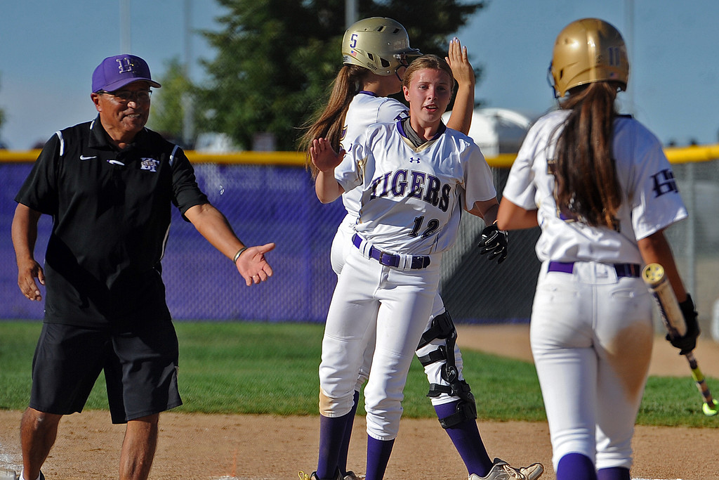 . Holy Family coach Mitch Martinez and Kaitlyn McKenzie (12) go to give Anna Martinez a high-five after their win over Berthoud on Tuesday, September, 11, 2018 at Holy Family High School in Broomfield, Colorado. (Sean Star/Loveland Reporter-Herald)