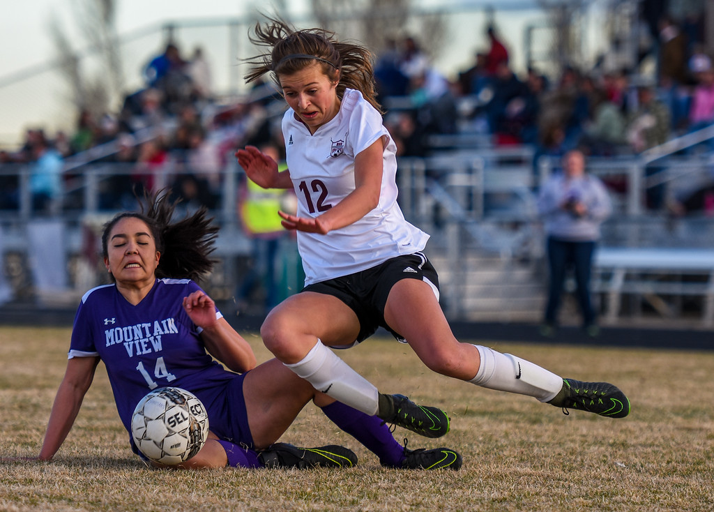 . Berthoud\'s Maddie Barcewski (12) gets tackled for a penalty by Mountain View\'s Madison Smithgall on Friday March 23, 2018 at Marr Field in Berthoud. (Cris Tiller / Loveland Reporter-Herald)
