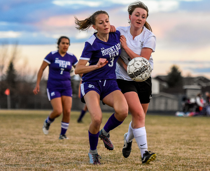 Mountain View's Jacey Paoli (3) battles with Berthoud's Aspen McCallum for ht eball on Friday March 23, 2018 at Marr Field in Berthoud. (Cris Tiller / Loveland Reporter-Herald)