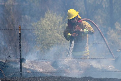 HANS PETER - DAILY DEMOCRAT Firefighters battled a grassfire near I-5, caused by a detached trailer.
