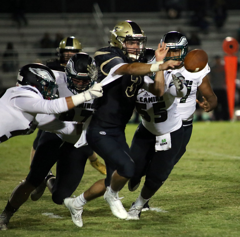 . MATT MURPHY - DAILY DEMOCRAT Pioneer High quarterback Alex Rodriguez throws a shovel pass as he is swarmed by El Camino defenders in a game on Sept. 7.