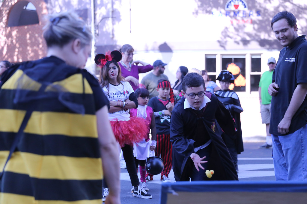 . SARAH DOWLING - DAILY DEMOCRAT Crowds gathered to play Chuck-a-Duck during Trick-or-Treat on Main Street in downtown Woodland.