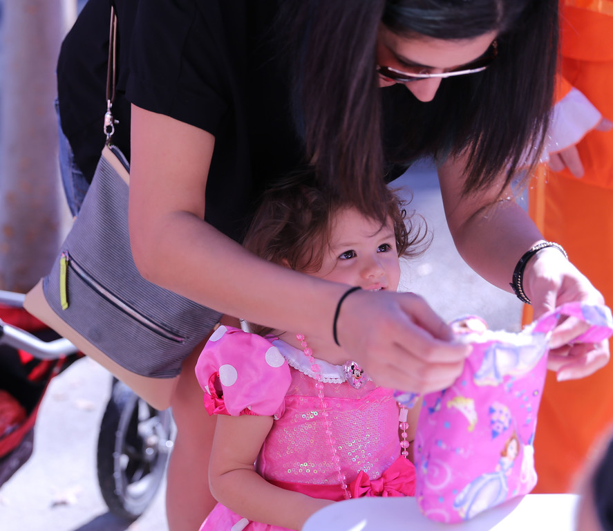 . SARAH DOWLING - DAILY DEMOCRAT A little girl gets some help during a Trick-or-Treat on Main Street in downtown Woodland.