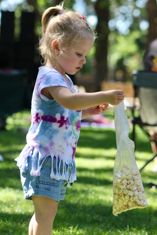 . HANS PETER - DAILY DEMOCRAT A tie-dye-wearing child eats kettle corn at the Woodland Hippie Festival.