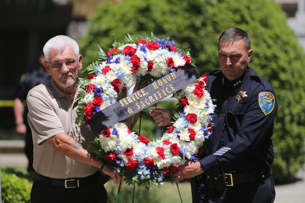 . DAILY DEMOCRAT FILE PHOTO On the left, Lee Refsland, Chair of the county�s retired peace officers association, presents a wreath with Davis� Deputy Chief David Delaini.