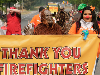 "Shaun Walker — The Times-Standard  Bigfoot, aka Percaos Waterman, 12, of Willow Creek, and Laurabelle Markussen of Weitchpec, right, walk behind a large ""Thank You Firefighters"" sign in the Bigfoot Days parade in Willow Creek on Saturday morning. The event featured food and craft vendors, skate ramps, live entertainment, car and motorcycle shows, and a softball tournament."
