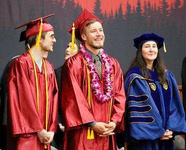 Shaun Walker — The Times-Standard  College of the Redwoods Salutatorian Alexander Knight, left, Valedictorian Caleb Dedmore, and Vice President of Instruction Angelina Hill stand on stage as the community college's 2018 graduation ceremony got underway Saturday morning.
