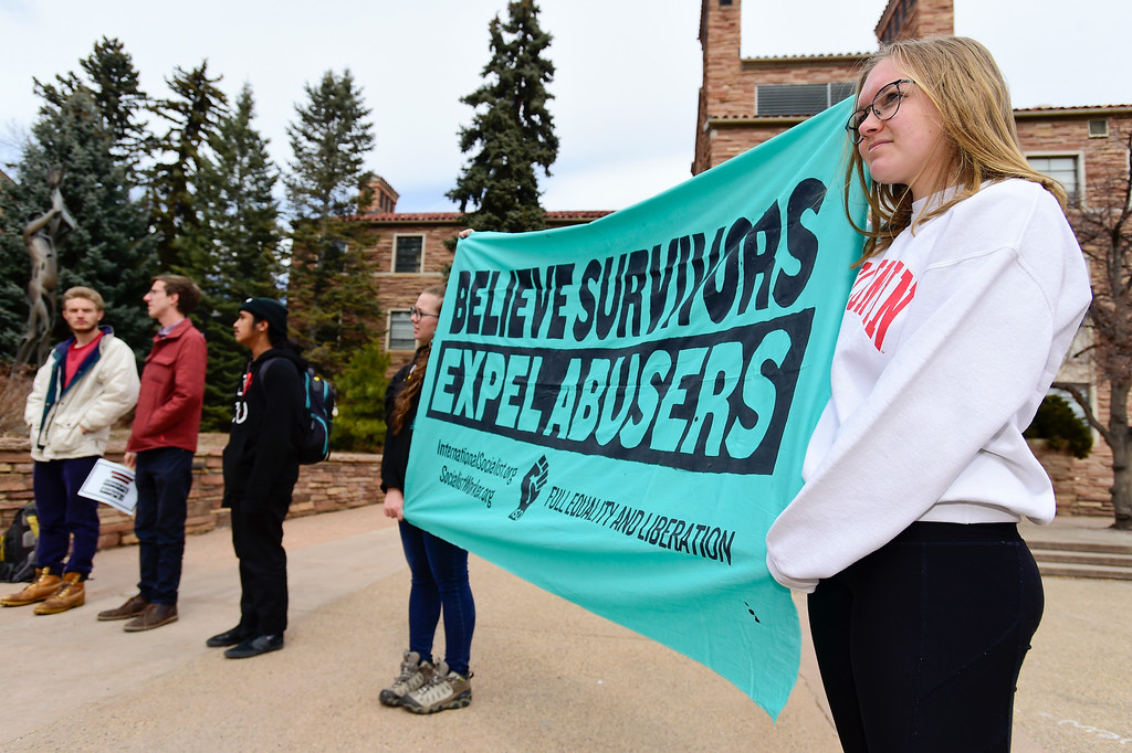 """. BOULDER, CO - MARCH 18:From right: University of Colorado students Anna Estes and Clark Zimmerman hold a \""""Believe Survivors Expel Abusers\"""" banner during a protest near the University Memorial Center on March 18, 2019. (Photo by Matthew Jonas/Staff Photographer)"""