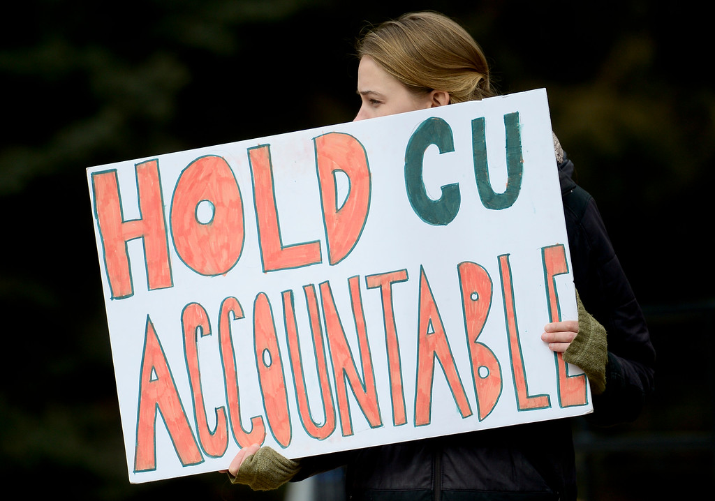 """. BOULDER, CO - MARCH 18:A protestor holds a sign reading \""""Hold CU Accountable\"""" during a protest near the University Memorial Center on March 18, 2019. (Photo by Matthew Jonas/Staff Photographer)"""