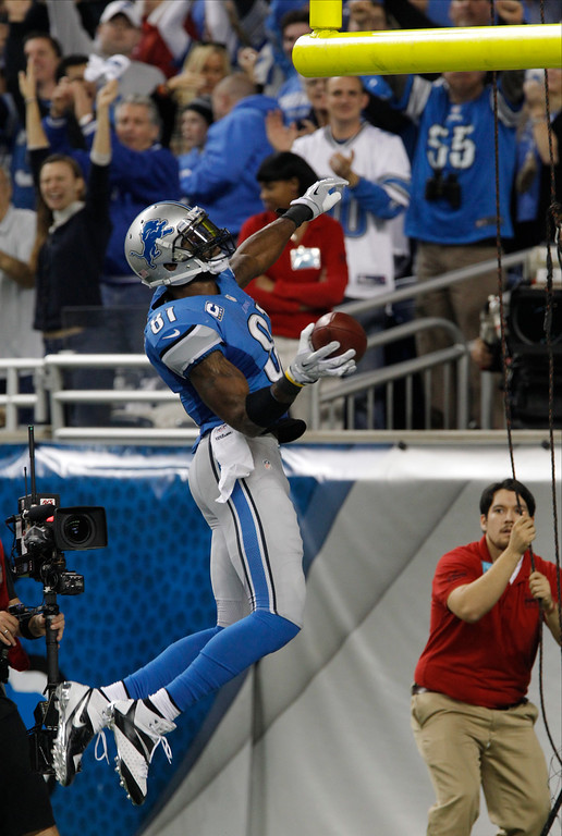 . Detroit Lions wide receiver Calvin Johnson (81) prepares to dunk the football after his 20-yard touchdown run during the third quarter of an NFL football game against the Green Bay Packers at Ford Field in Detroit, Thursday, Nov. 28, 2013. (AP Photo/Duane Burleson)