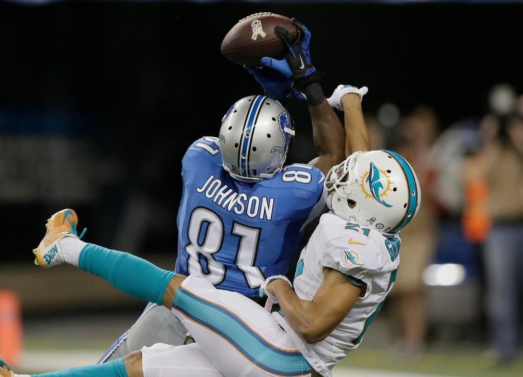 . Detroit Lions wide receiver Calvin Johnson (81), defended by Miami Dolphins cornerback Brent Grimes (21), catches 49-yard pass for a touchdown during the first half of an NFL football game in Detroit, Sunday, Nov. 9, 2014. (AP Photo/Duane Burleson)