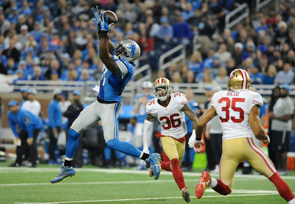 . Detroit Lions wide receiver Calvin Johnson misplays a catch defended by San Francisco 49ers cornerback Dontae Johnson (36) and free safety Eric Reid (35) during the first half of an NFL football game, Sunday, Dec. 27, 2015, in Detroit. (AP Photo/Jose Juarez)