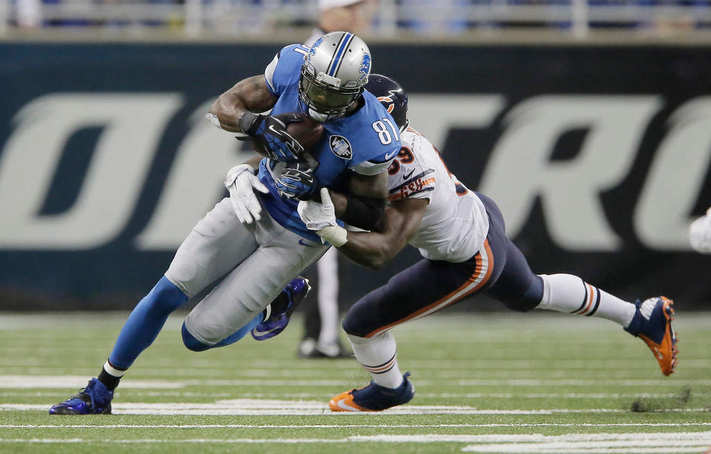 . Detroit Lions wide receiver Calvin Johnson (81) is tackled by Chicago Bears inside linebacker Christian Jones (59) after his 9-yard reception during the first half of an NFL football game in Detroit, Thursday, Nov. 27, 2014. With this catch, Johnson set a new NFL record for fewest games (115) to reach 10,000 career receiving yards. (AP Photo/Duane Burleson)