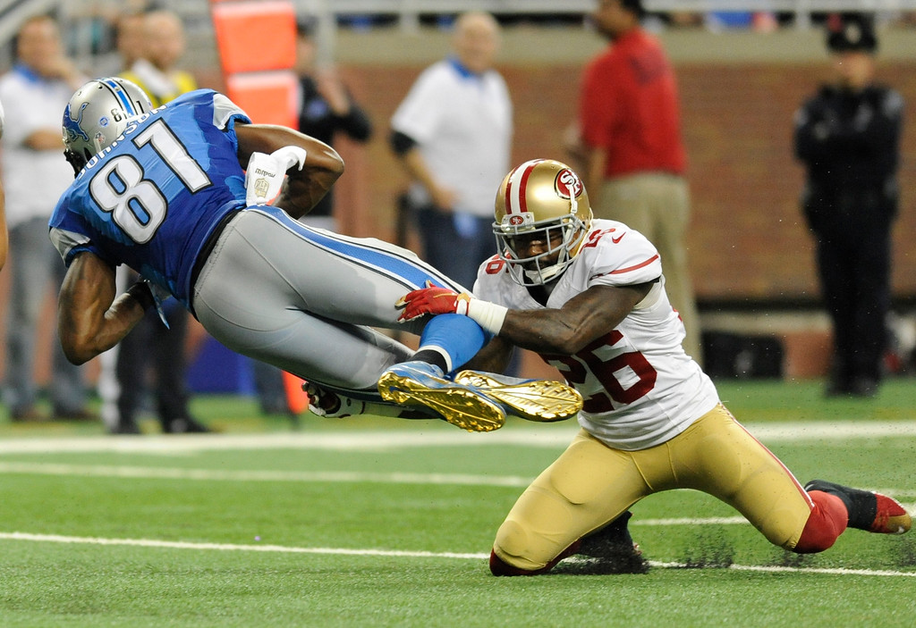 . Detroit Lions wide receiver Calvin Johnson (81) is tackled by San Francisco 49ers cornerback Tramaine Brock (26) during the second half of an NFL football game, Sunday, Dec. 27, 2015, in Detroit. (AP Photo/Jose Juarez)
