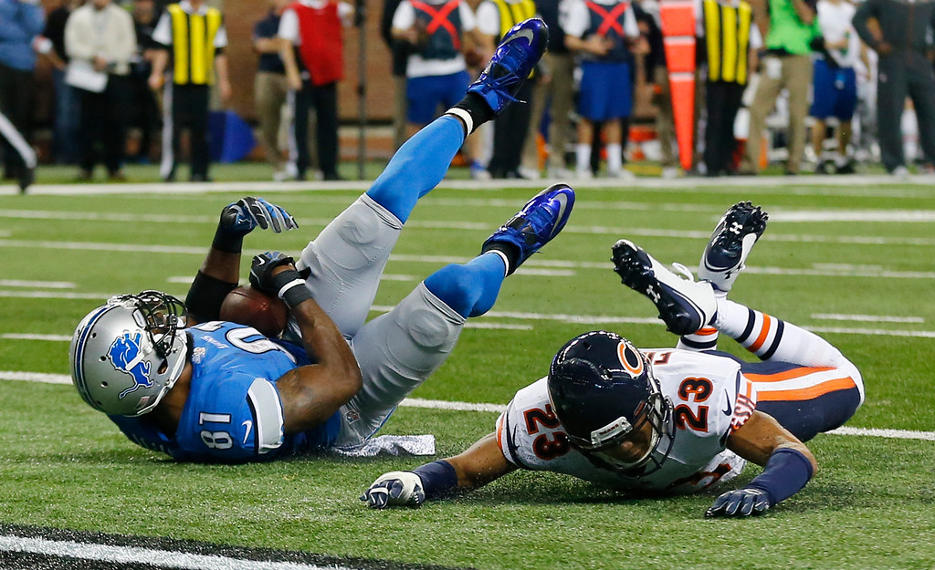 . Detroit Lions wide receiver Calvin Johnson (81), defended by Chicago Bears cornerback Kyle Fuller (23), falls into the end zone for a 25-yard reception for a touchdown during the first half of an NFL football game in Detroit, Thursday, Nov. 27, 2014. (AP Photo/Paul Sancya)