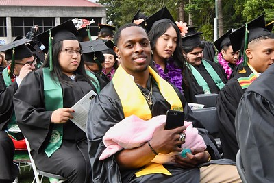 Khalil Ealy holds his 6-week old daughter Kahliyah Ealy before receiving his Criminology degree.  José Quezada—For Times-Standard