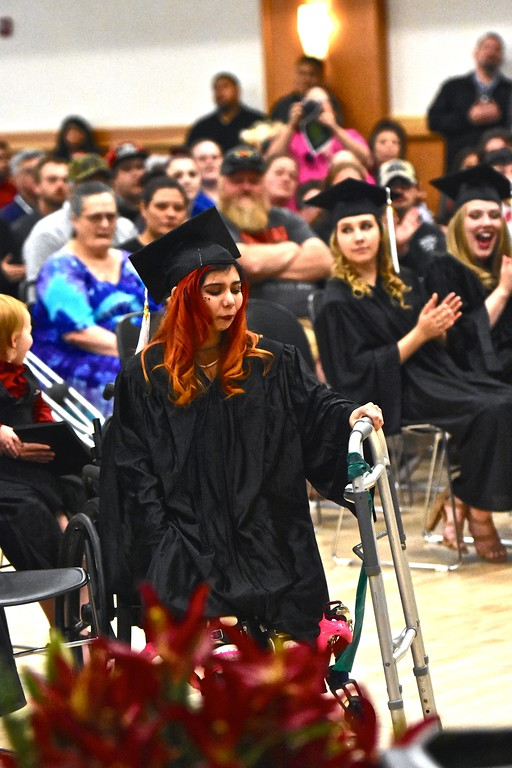 . Told by doctors she would not walk again, Taylor Marie Wheeler stands from her wheelchair before she made her way slowly forward to receive her Eel River Community School high school diploma Wednesday.  (José Quezada�For the Times-Standard)