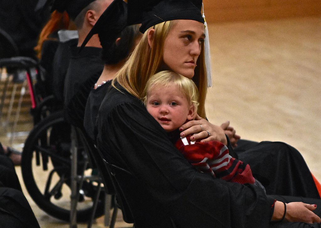 . A graduate sits with her young son. (José Quezada�For the Times-Standard)