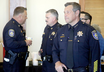 Shaun Walker — The Times-Standard  Outgoing Eureka Police Chief Andrew Mills, right, listens during a going away reception for him on Wednesday as new EPD Interim Chief Steve Watson, left, and Captain Brian Stephens talk.