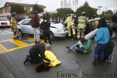 Shaun Walker — The Times-Standard  Reverand Sarah Potter covers the body of pretend fatal DUI accident victim Zalen Garen during a simulated student drunk driving accident scene in front of Arcata High School on Thursday morning as a student film crew documents it for an assembly. Every 15 Minutes is a two-day program which demonstrates to high school students the impact drinking and driving has on friends, families, and their community. The event included emergency responses from police, fire, ambulance, coroner, public works, and tow truck companies. The program will conclude with a mock funeral assembly for students.
