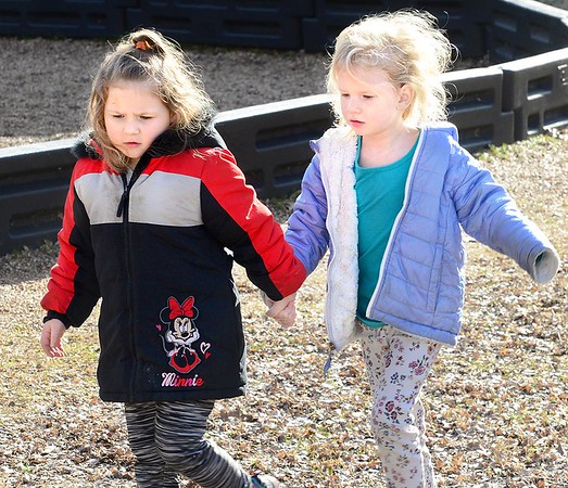 KEVIN HARVISON |<br /> Jefferson Early Childhood Center students Lilly Shepard, left and Carly Muse hold hands while walking around the JECC playground on recess.