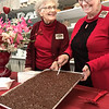 KEVIN HARVISON |<br /> Pictured from left, Twila Gray and Brenda Baxter cut into some chocolate Friday at North Town's JJ McAlester Antiques in preparation for visitors of the Chocolate Tour event.