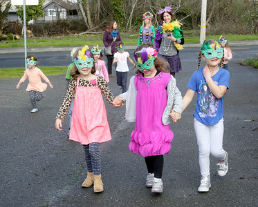 """Shaun Walker — The Times-Standard  Ella Willis, left, Alia Collins, 5, and Kelia Brandi, all 5, parade back to Mistwood Montessori in Eureka as part of their Fat Tuesday celebration. Students ages 3 to 6, teachers, and parents also had """"king cake"""" and the children caught beads from the teachers. It is a day when people eat all they want of everything and anything they want as the following day is Ash Wednesday, the beginning of a long fasting period for Christians."""