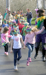 """Shaun Walker — The Times-Standard  Charlie Luker, left, and RyleeYorty, both 5, parade near Mistwood Montessori in Eureka as part of their Fat Tuesday celebration. Students ages 3 to 6, teachers, and parents also had """"king cake"""" and the children caught beads from the teachers. It is a day when people eat all they want of everything and anything they want as the following day is Ash Wednesday, the beginning of a long fasting period for Christians."""