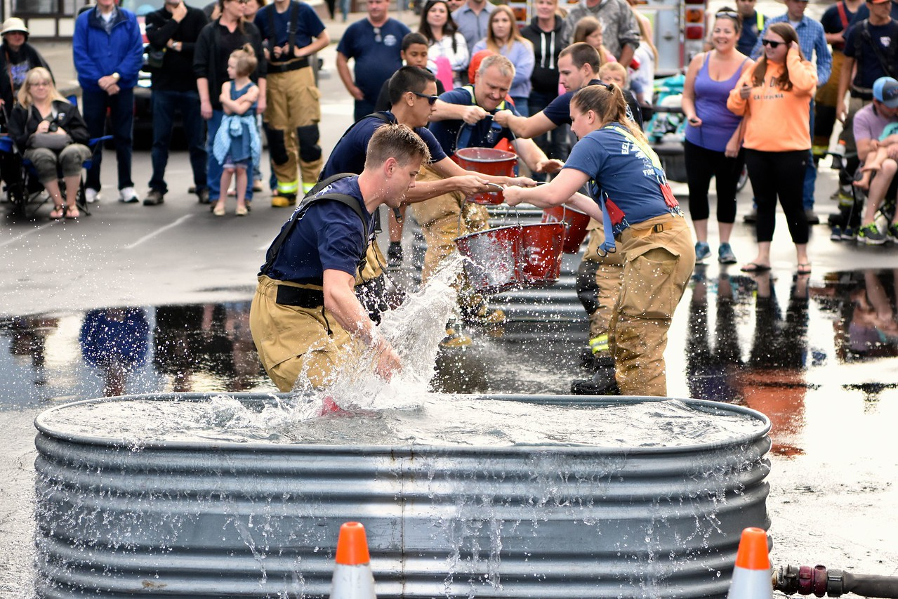 Explorers dip into the drink during the bucket brigade challenge. (José Quezada — For the Times-Standard)