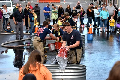 Loleta Explorers compete with their older Loleta Volunteer Fire Department firefighters in the bucket brigade. (José Quezada — For the Times-Standard)