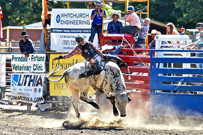 Colby Demo of Red Bluff keeps tight thighs on wild bull. José Quezada—For the Times-Standard
