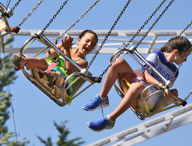 Shaun Walker — The Times-Standard  Lucia Maloney, 6, of Fortuna and sister Helena, 11, fly through the air at the Fortuna Rodeo carnival on Friday. The rodeo continues today with Fortuna Kiwanis pancake breakfast at 7 a.m., a parade down Main Street and more carnival at noon, rodeo action at 2 p.m., and gates open for Bulls, Broncs, Bands, and Brews at 6 p.m. at the Rohner Park Rodeo Grounds. For more information, go to fortunarodeo.com.