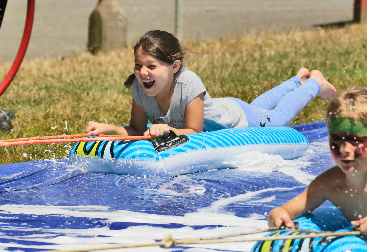 Shaun Walker — The Times-Standard  Natalie Marquez, 9, of Eureka gets pulled on soapy slide ride by Humboldt Bay firefighters in Sequoia Park during Eureka's Get Out and Play Day on Saturday. The annual city-wide event featured activities, games, rides, tours, and more for children and adults all over the city.