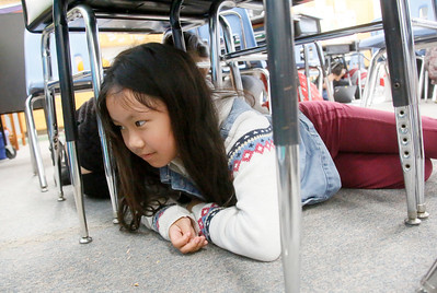 "Shaun Walker — The Times-Standard  Kiara Tayag goes for cover under her desk during the Great ShakeOut Earthquake Drills in Hollie Goodman's fourth grade class at Washington Elementary School in Eureka on Thursday morning. The worldwide event had over 55 million people registered to participate, of which nearly 40,000 were in Humboldt County, mostly students. Rescue teams, emergency managers, researchers, and school safety advocates, all agree that the drill's ""Duck, Cover, and Hold On"" is the appropriate action to reduce injury and death during earthquakes, according to the event website at earthquakecountry.org. ""Methods like standing in a doorway, running outside, and 'triangle of life' method are considered dangerous and are not recommended."""