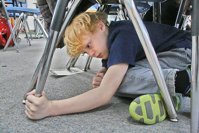 "Shaun Walker — The Times-Standard  Gabriel Wrate takes cover under his desk during the Great ShakeOut Earthquake Drills in Hollie Goodman's fourth grade class at Washington Elementary School in Eureka on Thursday morning. The worldwide event had over 55 million people registered to participate, of which nearly 40,000 were in Humboldt County, mostly students. Rescue teams, emergency managers, researchers, and school safety advocates, all agree that the drill's ""Duck, Cover, and Hold On"" is the appropriate action to reduce injury and death during earthquakes, according to the event website at earthquakecountry.org. ""Methods like standing in a doorway, running outside, and 'triangle of life' method are considered dangerous and are not recommended."""
