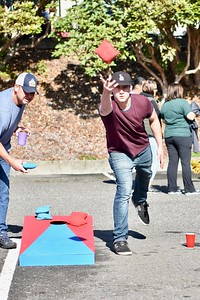 Cory Kent tosses his bean bag in a corn hole game, as his competition Jeremiah Joyner sets up for his toss in the parking lot of the tailgate party. Jose Quezada—For Times-Standard