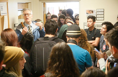 Shaun Walker — The Times-Standard  Alexander Enyedi, Provost and Vice President for Academic Affairs, talks with students in the hallway outside his office at Humboldt State University where students had been chanting and demanding to see administrators during a walkout to protest planned budget cuts Wednesday afternoon.