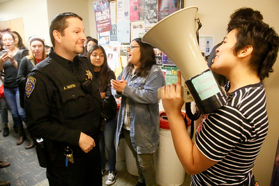 Shaun Walker — The Times-Standard  University Police Officer Andy Martin talks with student organizer Moxie Alvarnaz in the hallway outside the president's office at Humboldt State University where students had been chanting and demanding to see administrators during a walkout to protest planned budget cuts Wednesday afternoon.