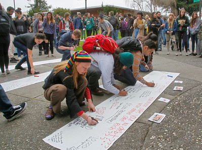 Shaun Walker — The Times-Standard  Environmental studies major Gabrielle Smith and others write their grievances and about their student debts on the Humboldt State University quad during a walkout to protest planned budget cuts Wednesday afternoon.