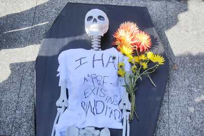 "Shaun Walker — The Times-Standard  A skeleton with the words ""I had a 'pre-existing condition'"" on it was carried to the rally in a slow procession."