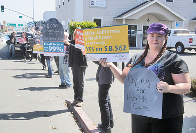 "Shaun Walker — The Times-Standard  Diamond Moebus of Samoa holds signs at a rally to voice support for the Healthy California Act, SB 562, in front of Assembly Member Jim Wood's offices in Eureka on Wednesday. The bill would create a single-payer ""Medicare for All"" health care system in California. The bill has already passed the State Senate, but rally attendees and rally organizers at The North Coast People's Alliance want Wood to strongly support it and for it to make it out of the assembly. Activists in both Ukiah and Santa Rosa hosted parallel events yesterday at Woods district offices there."