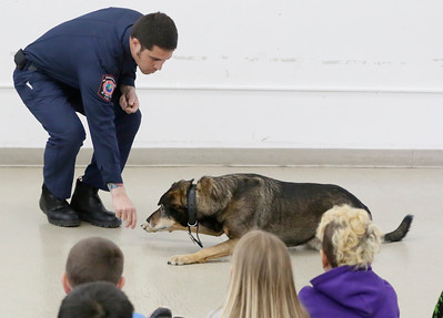 Shaun Walker — The Times-Standard  Humboldt Bay Firefighter Yolla Montalbin has Cali the Fire Dog demonstrate staying low and crawling along the floor during a presentation to second-graders at Washington Elementary School in Eureka on Friday.