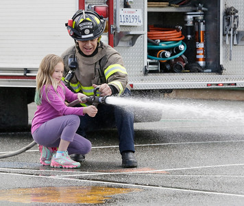 Shaun Walker — The Times-Standard  Second-grader Alison Gower helps Humboldt Bay Firefighter Brandon Harlander spray water on Friday.