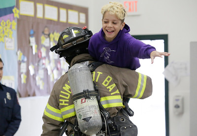 Shaun Walker — The Times-Standard  Second-grader Bo Landry smiles as Humboldt Bay Firefighter Brandon Harlander pretends to rescue him during at Washington Elementary School in Eureka on Friday.
