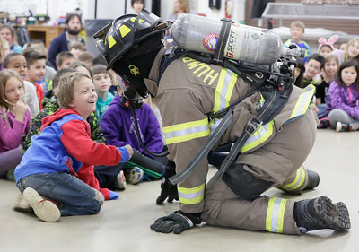 Shaun Walker — The Times-Standard  Second-grader Jamison Blevin, left, smiles as Humboldt Bay Firefighter Brandon Harlander crawls around in full gear during a safety presentation at Washington Elementary School in Eureka on Friday.